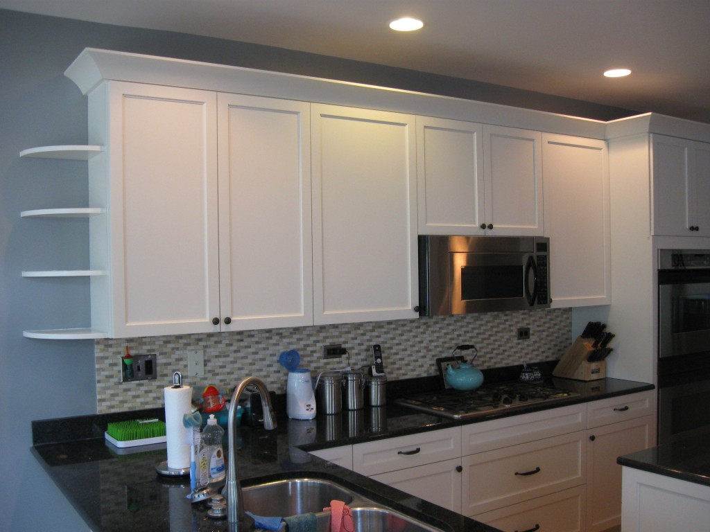 These cabinets in Glen Ellyn were refaced in maple with a linen white finish and no glaze. The inside edge of the doors has a subtle arch profile that is echoed in the crown molding.